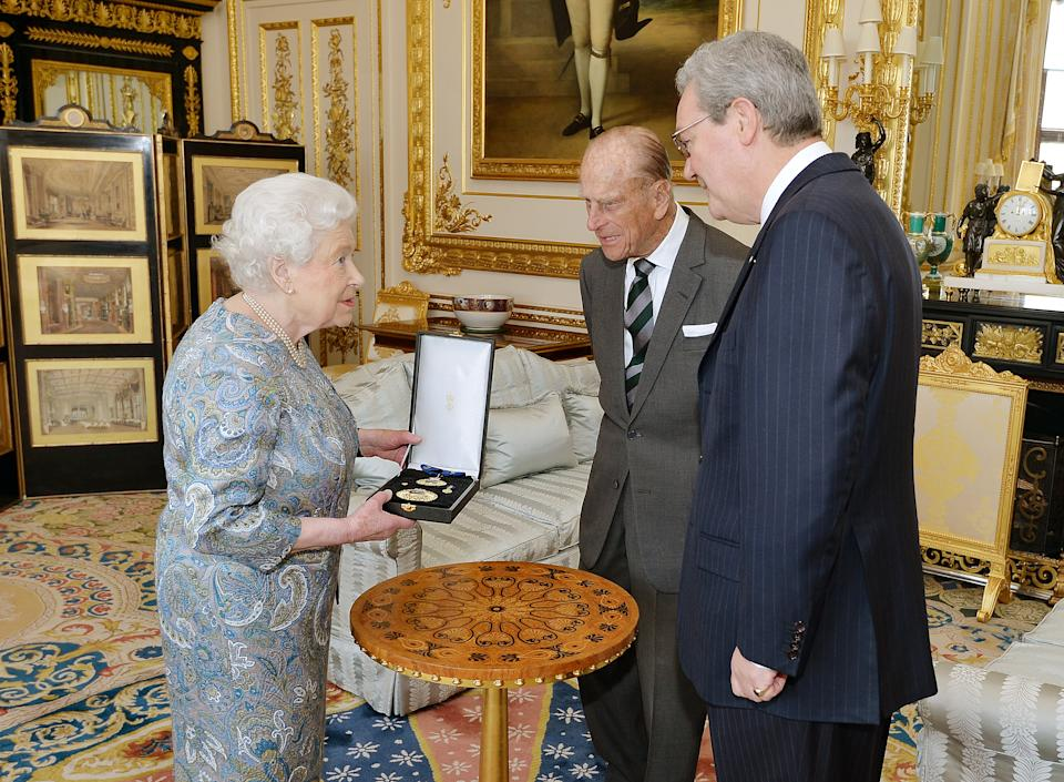 Queen Elizabeth II talks with the Australian High Commissioner Alexander Downer (R) as she prepares to present the Prince Philip, Duke of Edinburgh with the Insignia of a Knight of the Order of Australia, in the white drawing room at Windsor Castle on April 22, 2015 in Windsor, England.