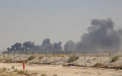 Smoke billows from an Aramco oil facility in Abqaiq about 60km (37 miles) southwest of Dhahran in Saudi Arabia - Credit: AFP