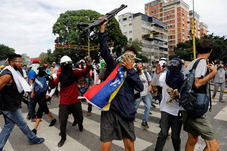 Opposition supporters show a shotgun that they snatched from riot police during a rally against President Nicolas Maduro in Caracas