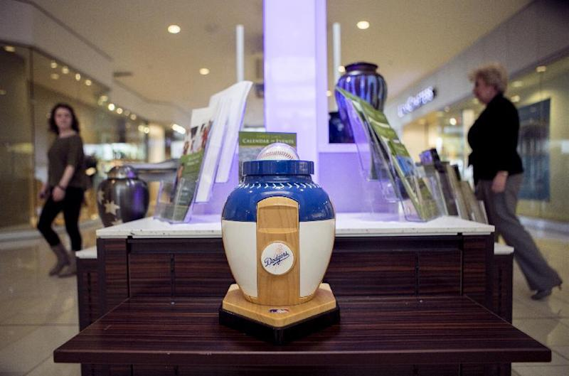 In this Thursday, Jan. 30, 2014, shows a Los Angeles Dodgers baseball sports cremation urn displayed at the Forest Lawn stand at the Glendale Galleria mall in Glendale, Calif. Forest Lawn, famous as the final resting place for everyone from Al Jolson to Michael Jackson, has begun staffing outlets at shopping malls, reasoning that planning for death, either for a loved one or yourself, might not be quite as intimidating for some people if it takes place in a lively, happy place like a mall rather than the more somber confines of a cremation home. (AP Photo/Damian Dovarganes)