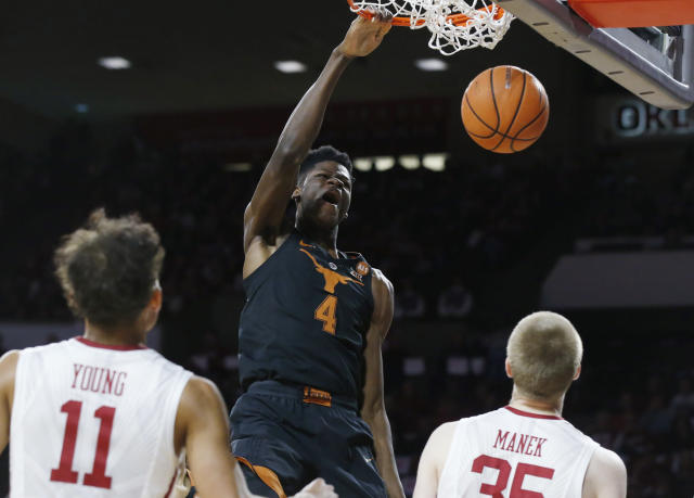 Texas forward Mohamed Bamba (4) dunks in front of Oklahoma guard Trae Young (11) and forward Brady Manek (35) in the first half of an NCAA college basketball game in Norman, Okla., Saturday, Feb. 17, 2018. (AP Photo/Sue Ogrocki)