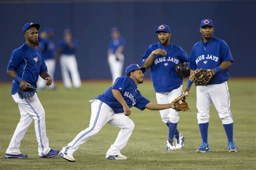 Maicer Izturis, center left, reaches a stray ball in front of Jose Reyes, left, ; Emilio Bonifacio, second from right, and Edwin Encarnacion, right, as the Toronto Blue Jays have a practice session in Toronto on Monday April 1, 2013 as they prepare for their opening day of the new season. (AP Photo/The Canadian Press, Chris Young)