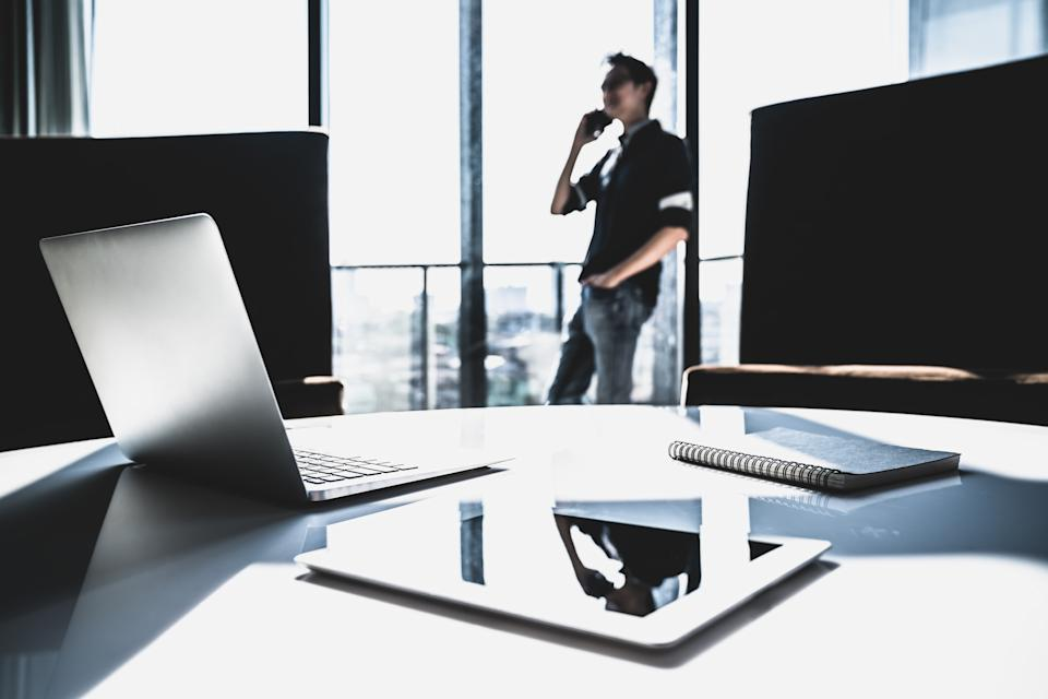 Asian man or business owner using mobile phone call in modern office. Communication gadget technology, freelance, startup SME entrepreneur concept. Dramatic silhouette. Selective focus on laptop