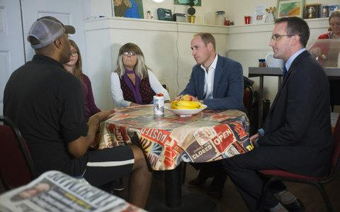 Prince William, Duke of Cambridge speaks with people in the drop in cafe which is geared toward helping the homeless - Credit: David Rose - WPA Pool / Getty Images