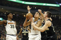 Denver Nuggets' Michael Porter Jr. looks to shoot against multiple Milwaukee Bucks defenders during the first half of an NBA basketball game Friday, Jan. 31, 2020, in Milwaukee. (AP Photo/Aaron Gash)