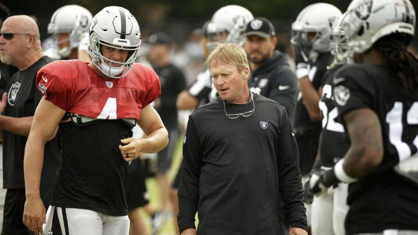 Oakland Raiders head coach Jon Gruden talks with quarterback Derek Carr during NFL football practice Wednesday, Aug. 8, 2018, in Napa, Calif. Both the Oakland Raiders and the Detroit Lions held a joint practice before their upcoming preseason game on Friday. (AP Photo/Eric Risberg)