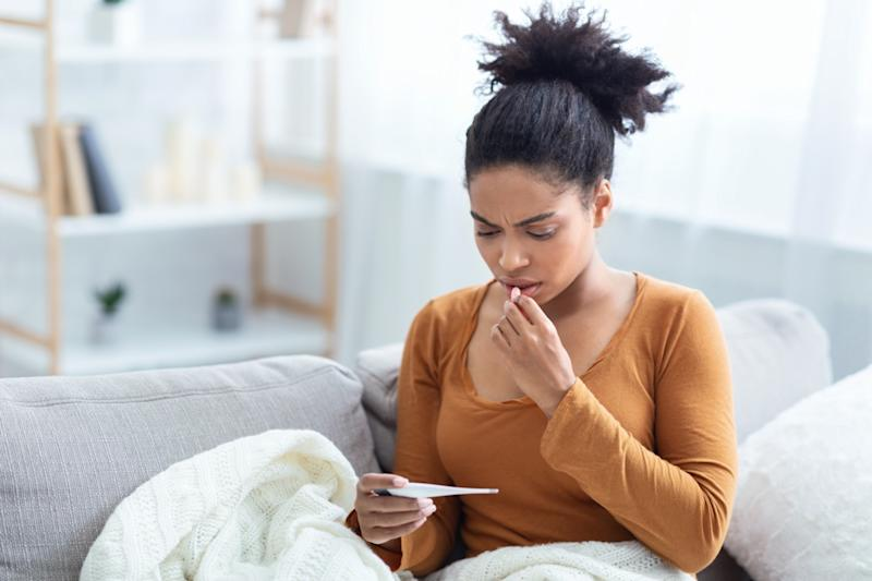 Lady Holding Thermometer Having Fever Measuring Body Temperature Sitting On Sofa At Home