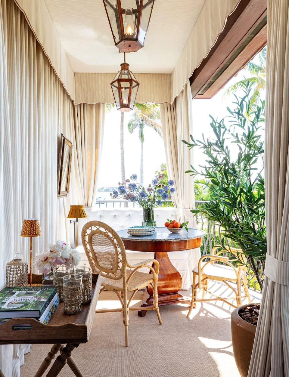 """<p>Channeling Marrakech glamour, this breezy loggia feels like a far-off escape. <a href=""""http://www.annabraund.com/"""" rel=""""nofollow noopener"""" target=""""_blank"""" data-ylk=""""slk:Braund"""" class=""""link rapid-noclick-resp"""">Braund</a> wrapped the space with custom drapes from <a href=""""http://www.perennialsandsutherland.com/our-companies/perennials-fabrics/index.html"""" rel=""""nofollow noopener"""" target=""""_blank"""" data-ylk=""""slk:Sutherland Perennials"""" class=""""link rapid-noclick-resp"""">Sutherland Perennials</a> and added rattan chairs from <a href=""""https://bungalowclassic.com/"""" rel=""""nofollow noopener"""" target=""""_blank"""" data-ylk=""""slk:Bungalow Classic"""" class=""""link rapid-noclick-resp"""">Bungalow Classic</a> and an antique cherrywood table from <a href=""""https://robuck.co/"""" rel=""""nofollow noopener"""" target=""""_blank"""" data-ylk=""""slk:Robuck"""" class=""""link rapid-noclick-resp"""">Robuck</a> to create an intimate alfresco sitting space. </p>"""