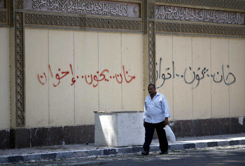 "An Egyptian man walks past Arabic graffiti Arabic that reads, ""traitor will betray the brotherhood"", on an outer wall of the presidential palace, in Cairo, Egypt, Friday, June 28, 2013, days ahead of mass protests against the country's Islamist President Mohammed Morsi. (AP Photo/Hassan Ammar)"
