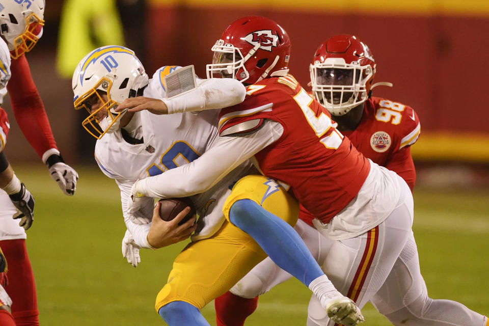 Los Angeles Chargers quarterback Justin Herbert is sacked by Kansas City Chiefs defensive end Alex Okafor, right, during the second half of an NFL football game, Sunday, Jan. 3, 2021, in Kansas City. (AP Photo/Charlie Riedel)