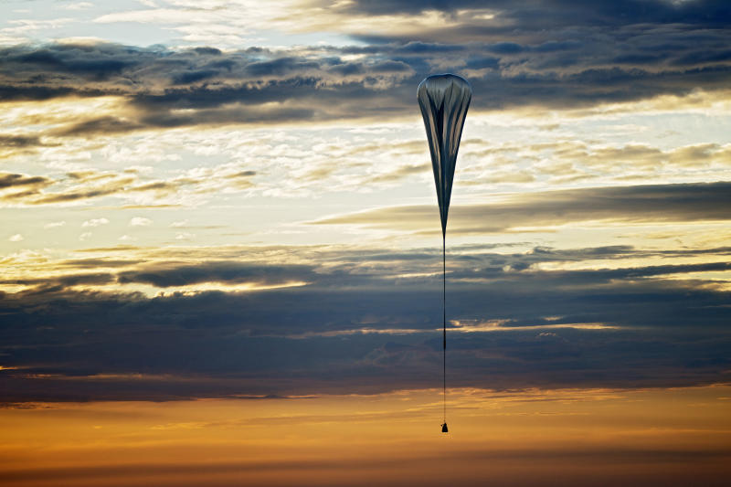 "In this July 25, 2012 photo provided by Red Bull Stratos, a balloon lifts up during the second manned test flight for Red Bull Stratos in Roswell, N.M. It's described as a ""40-acre dry cleaner bag,"" that, when first filled, will stretch 55 stories high. On Monday, this special ultra-thin helium balloon is scheduled to liftoff from Roswell, N.M., to carry ""Fearless Felix"" Baumgartner 23 miles into the stratosphere for what he hopes will be a history-making, sound barrier-breaking skydive. (AP Photo/Red Bull Stratos)"