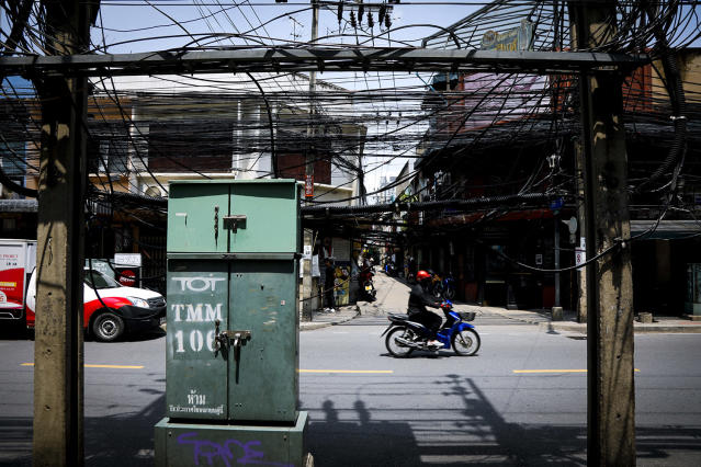 <p>A man rides a scooter past a clutter of cables along a street in Bangkok, Thailand, May 18, 2017. Talks of placing existing overhead power lines and cables underground are underway. (Photo: Diego Azubel/EPA) </p>