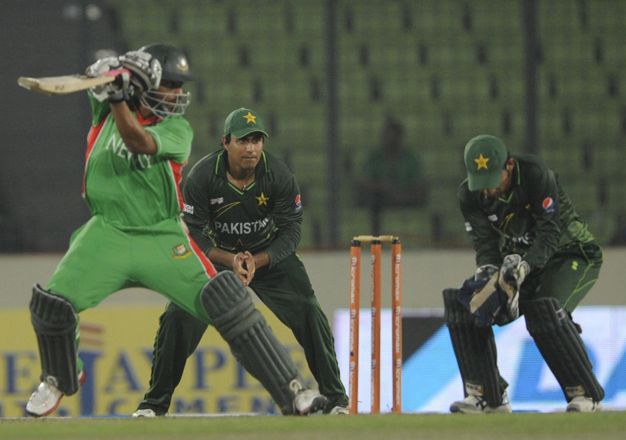 Bangladshi batsman Tamim Iqbal (L) plays a shot as Pakistan cricketers Nasir Jamshed (C) and Sarfraz Ahmed (R) react during the one day international (ODI) Asia Cup cricket   match between Bangladesh and Pakistan at The Sher-e-Bangla National Cricket Stadium in Dhaka on March 11, 2012.