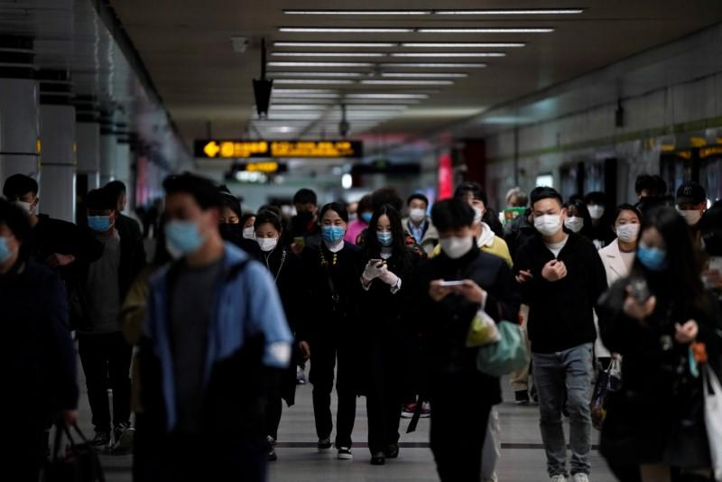 Passengers wearing face masks are seen at a subway station after the city's emergency alert level for coronavirus disease (COVID-19) was downgraded, in Shangha