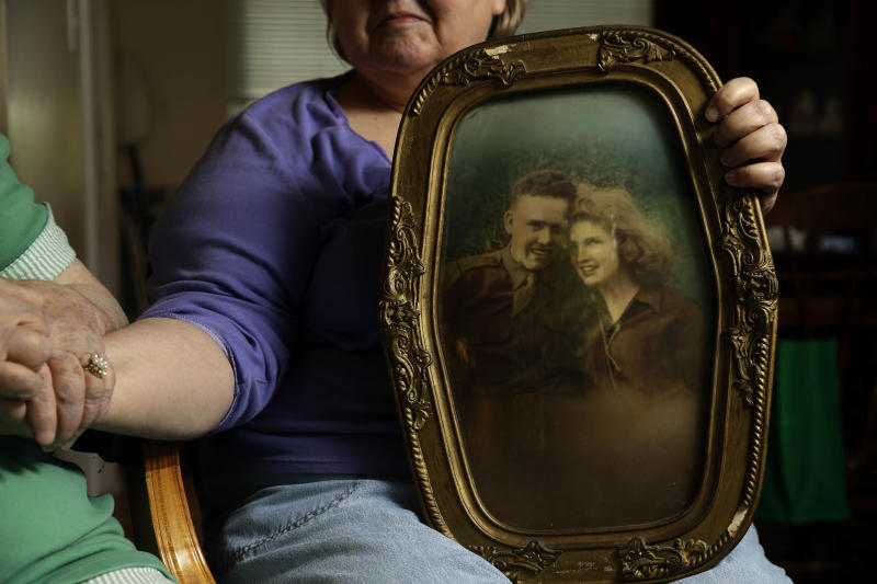 """In this photo taken Monday, July 1, 2013, in Chapel Hill, N.C., Shelia Reese, right, holds hands with her mother Chris Tench while holding a portrait of Tench and her father Kenneth F. Reese, a soldier who is still Missing In Action from the Korean War. Tench, who was later remarried, has never known what happened to her husband. The Pentagon's effort to account for tens of thousands of Americans missing in action from foreign wars is so inept, mismanaged and wasteful that it risks descending from """"dysfunction to total failure,"""" according to an internal study suppressed by military officials. (AP Photo/Gerry Broome)"""