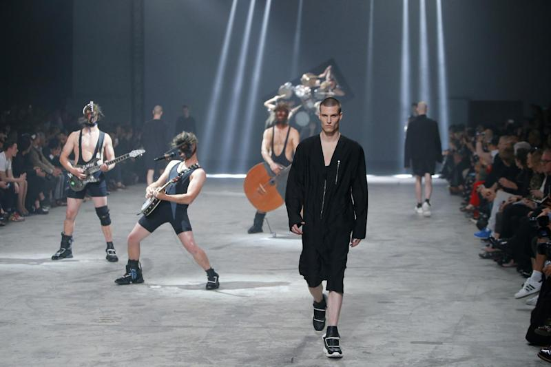 A model wears a creation by fashion designer Rick Owens as part of his men's fashion Spring-Summer 2014 collection, presented Thursday, June 27, 2013 in Paris, as Estonian metal/punk band Winny Puhh performs live, rear . (AP Photo/Francois Mori)