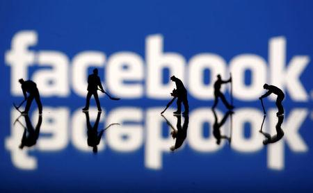 Figurines are seen in front of the Facebook logo in this illustration taken March 20, 2018. REUTERS/Dado Ruvic