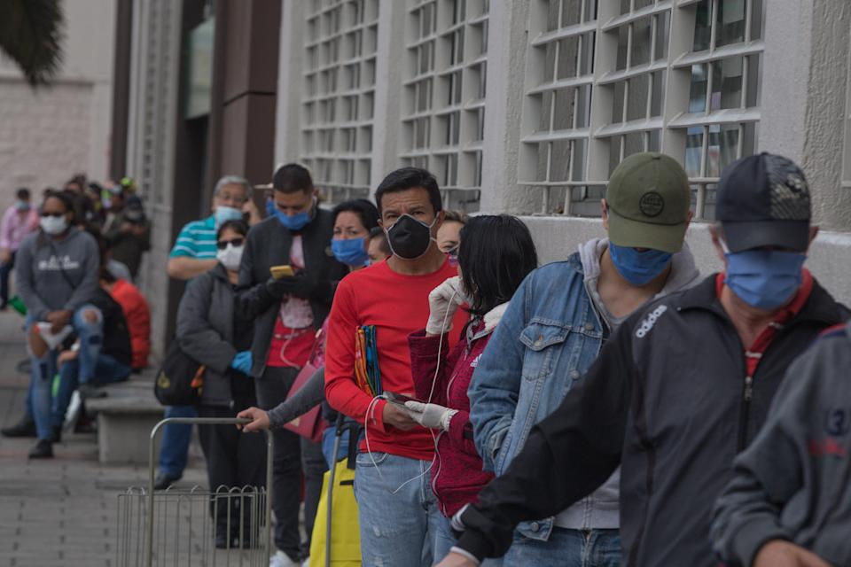 BOGOTA, COLOMBIA - APRIL 02: A long line of people wearing protective masks outside a supermarket during the national quarantine to claim gov aid in Bogota, Colombia on April 02, 2020. During the national quarantine, there are crowds in supermarkets to claim gov aid, mostly from parents and elderly residents. (Photo by Juancho Torres/Anadolu Agency via Getty Images)