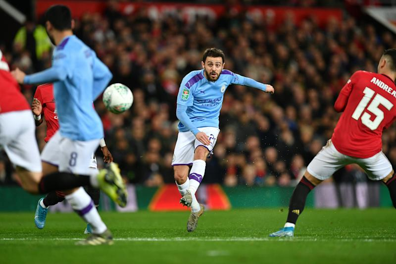Manchester City's Portuguese midfielder Bernardo Silva (C) scores the opening goal during the English League Cup semi-final first leg football match between Manchester United and Manchester City at Old Trafford in Manchester, north west England on January 7, 2020. (Photo by Paul ELLIS / AFP) / RESTRICTED TO EDITORIAL USE. No use with unauthorized audio, video, data, fixture lists, club/league logos or 'live' services. Online in-match use limited to 75 images, no video emulation. No use in betting, games or single club/league/player publications. / (Photo by PAUL ELLIS/AFP via Getty Images)