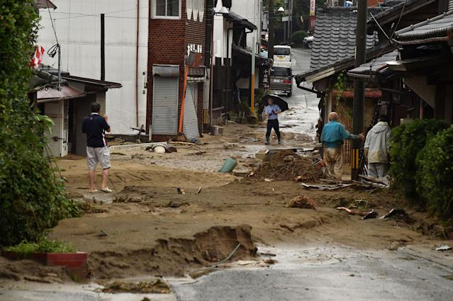 <p>Local residents stand outside their homes on a street filled with mud and silt following heavy flooding in Asakura, Fukuoka prefecture, on July 6, 2017. (Photo: Kazuhiro Nogi/AFP/Getty Images) </p>