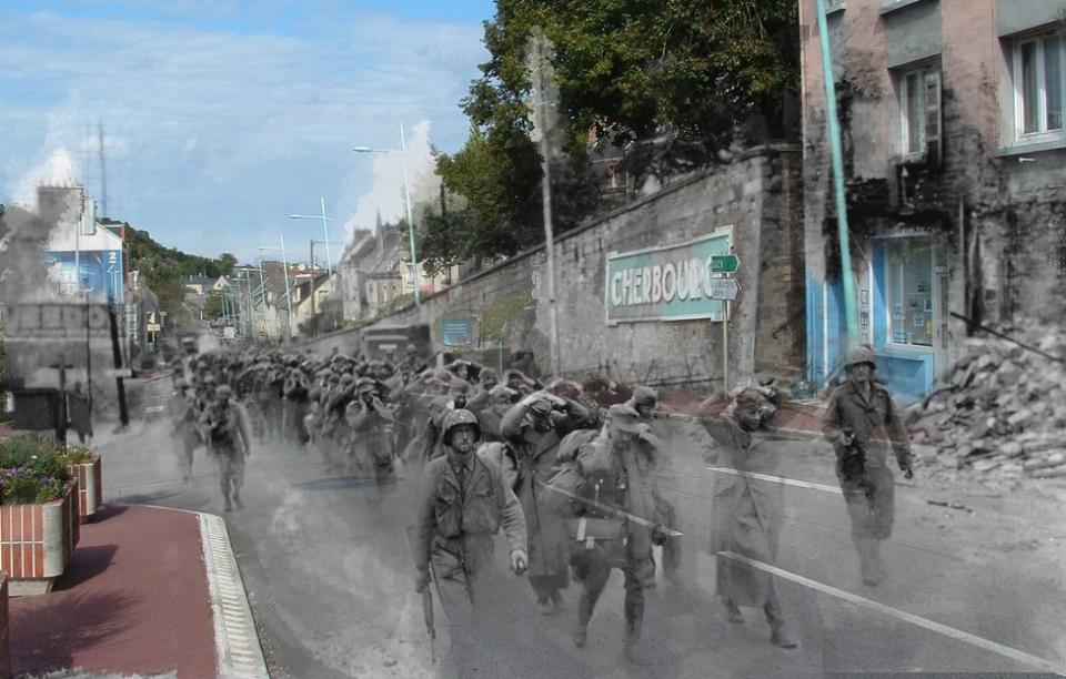 """The photograph shows almost ghost-like figures from the past appearing in the present-day town. American soldiers march German prisoners of war through the city of Cherbourg.<br><br>(<a href=""""http://www.flickr.com/photos/hab3045/collections/72157629378669812/"""" rel=""""nofollow noopener"""" target=""""_blank"""" data-ylk=""""slk:Courtesy of Jo Teeuwisse"""" class=""""link rapid-noclick-resp"""">Courtesy of Jo Teeuwisse</a>)"""