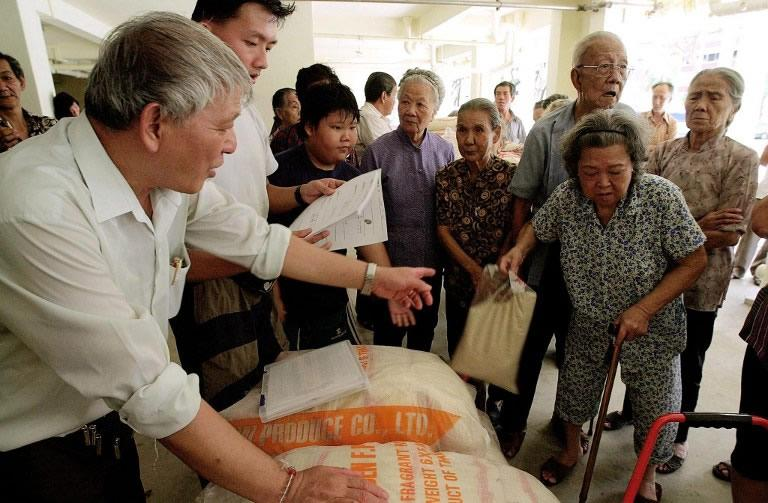 Poor elderly Singaporeans receive a 5-kg pack of rice from the Moral Care Society in Singapore. (AFP FILE PHOTO/Roslan RAHMAN)