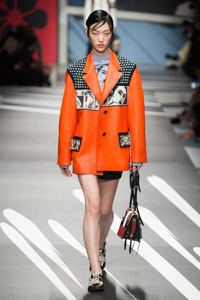 <p><i>Model wears an orange coat with graphic, comic-book images from the SS18 Prada collection. (Photo: ImaxTree) </i></p>