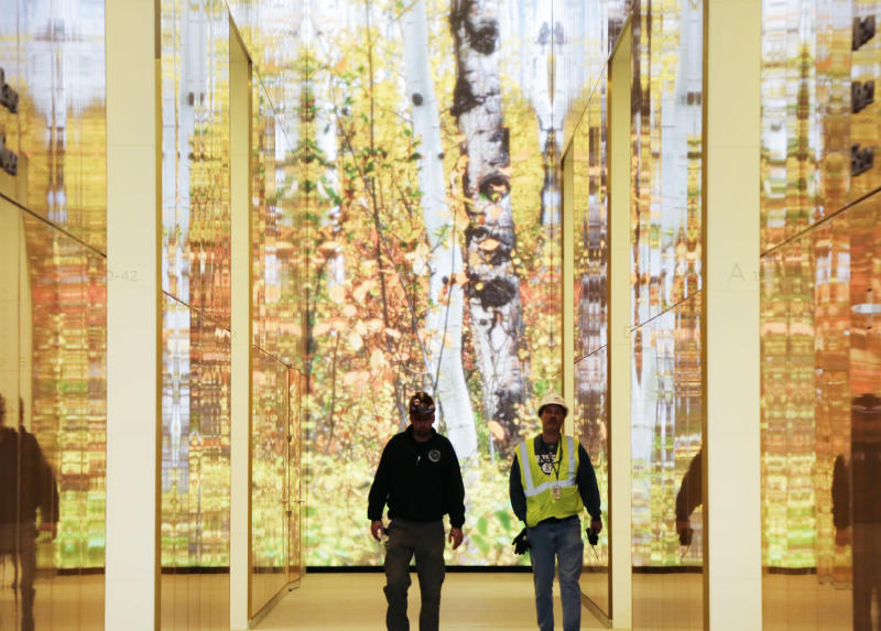 Workers walk past a video art installation in the lobby of 4 World Trade Center, Thursday, Nov. 7, 2013, in New York. The 978-foot building designed by Pritzker Prize-winning architect Fumihiko Maki will open on Wednesday, Nov. 13. (AP Photo/Mark Lennihan)