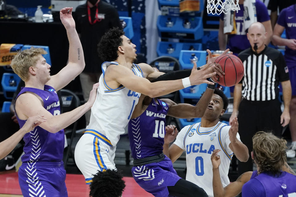 UCLA's Jules Bernard (1) reaches for a rebound between Abilene Christian's Kolton Kohl, left, and Reggie Miller (10) during the first half of a college basketball game in the second round of the NCAA tournament at Bankers Life Fieldhouse in Indianapolis Monday, March 22, 2021. (AP Photo/Mark Humphrey)