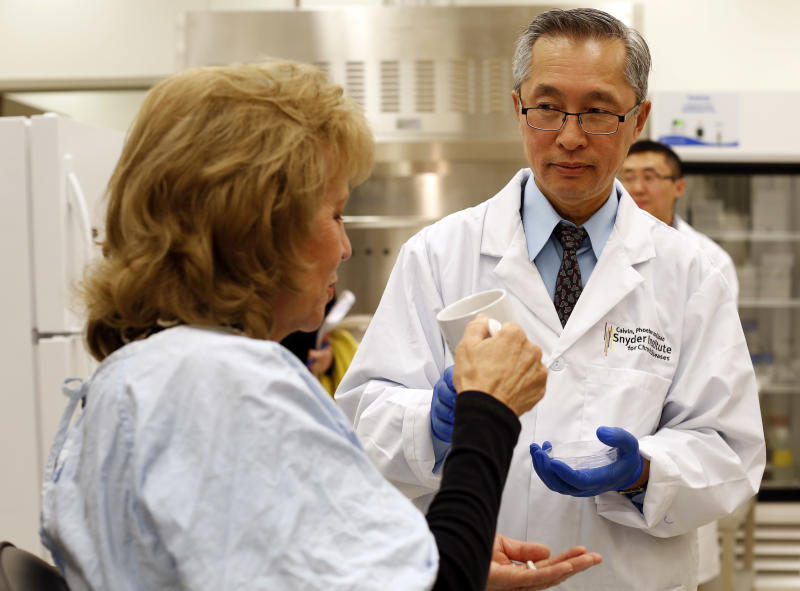 """Dr. Thomas Louie, right, an infectious disease specialist at the University of Calgary, administers fecal transplant pills to a patient in his lab in Calgary, Alberta, Canada on Thursday, Sept. 26, 2013. """"There's no stool left - just stool bugs. These people are not eating poop,"""" and there are no smelly burps because the contents aren't released until they're well past the stomach, Louie said. (AP Photo/The Canadian Press, Jeff McIntosh)"""