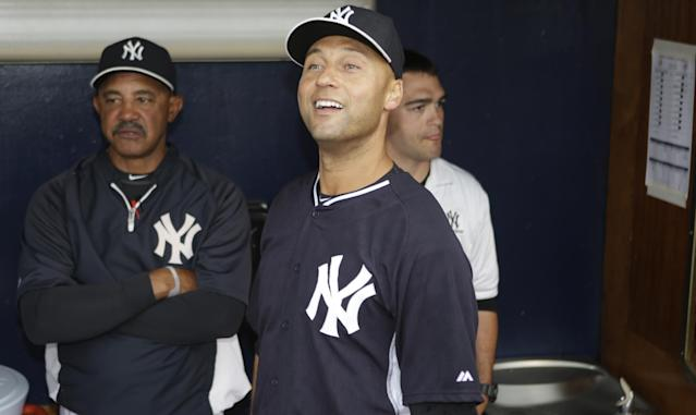 New York Yankees shortstop Derek Jeter, center, and bench coach Tony Pena, left, watch highlights of Jeter's career on a giant video screen in center field during an brief ceremony honoring him for his Turn 2 Foundation prior to a spring exhibition baseball game against the Miami Marlins, in Tampa, Fla., Saturday, March 29, 2014. The game was canceled due to rain. (AP Photo/Kathy Willens)
