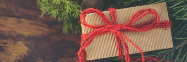 brown paper package wrapped with a red string sitting on a wooden table with pine branches surrounding