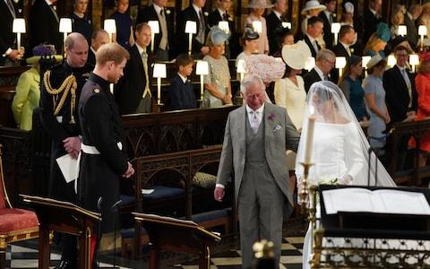 Prince Harry looks at his bride, Meghan Markle, as she arrives accompanied by the Prince of Wales in St George's Chapel  - Credit: Jonathan Brady/PA