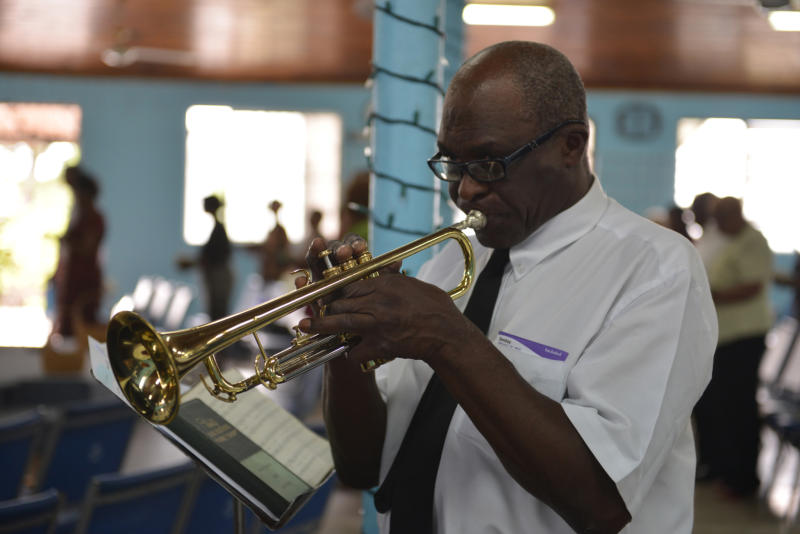 "In this Sunday, Feb. 16, 2014, photo, music instructor Winston ""Sparrow"" Martin is shown playing a trumpet, leading a band of former students at a church service in Kingston, Jamaica. The veteran bandmaster has provided a solid musical foundation for numerous boys at Alpha Boys' School, a residential vocational school in Kingston which has been a cornerstone of Jamaica's prolific musical culture for over a century. (AP Photo/David McFadden)"