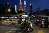 A motorcyclist wears a face mask with the background of Twin Towers in downtown Kuala Lumpur, Malaysia, Monday, Jan. 11, 2021. Prime Minister Muhyiddin Yassin says Malaysia's health care system is at a breaking point as he announced new movement curbs, including near-lockdown in Kuala Lumpur and several high-risk states to rein in a spike in coronavirus cases.(AP Photo/Vincent Thian)