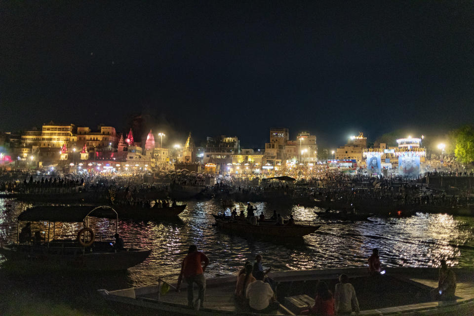 Tourists sit on a boat and watch Hindu priests perform evening rituals on the banks of the River Ganges in Varanasi, India, Sunday, March 14, 2021. Varanasi is among the world's oldest cities, and millions of Hindu pilgrims gather annually here for ritual bathing and prayers in the Ganges River, considered holiest by Hindus. (AP Photo/Rajesh Kumar Singh)