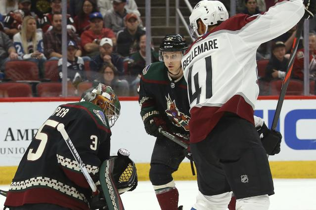 Arizona Coyotes goaltender Darcy Kuemper (35) makes a save between Colorado Avalanche left wing Pierre-Edouard Bellemare (41) and Coyotes defenseman Aaron Ness (42) during the first period of an NHL hockey game Saturday, Nov. 2, 2019, in Glendale, Ariz. (AP Photo/Ross D. Franklin)