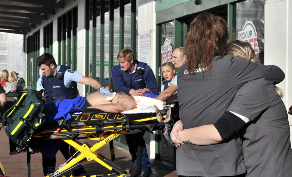 Supermarket staff embrace as police officers take a victim to an ambulance outside a Countdown supermarket in central Dunedin, New Zealand, Monday May 10, 2021. A man began stabbing people at a New Zealand supermarket Monday, wounding five people, three of them critically, according to authorities. (Christine O'Connor/Otago Daily Times via AP)