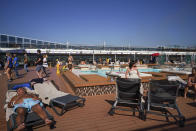 Passengers enjoy the sun by a swimming pool on board the MSC Grandiosa cruise ship in Civitavecchia, near Rome, Wednesday, March 31, 2021. MSC Grandiosa, the world's only cruise ship to be operating at the moment, left from Genoa on March 30 and stopped in Civitavecchia near Rome to pick up more passengers and then sail toward Naples, Cagliari, and Malta to be back in Genoa on April 6. For most of the winter, the MSC Grandiosa has been a lonely flag-bearer of the global cruise industry stalled by the pandemic, plying the Mediterranean Sea with seven-night cruises along Italy's western coast, its major islands and a stop in Malta. (AP Photo/Andrew Medichini)
