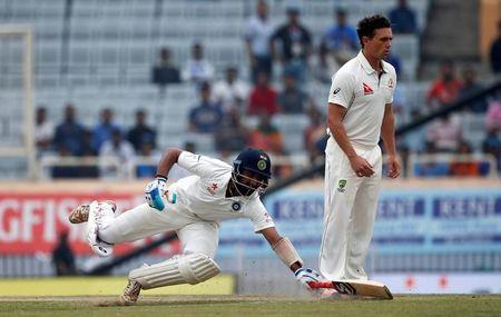 Cricket - India v Australia - Third Test cricket match - Jharkhand State Cricket Association Stadium, Ranchi, India - 19/03/17 - India's Cheteshwar Pujara dives to avoid being run out as Australia's Steve O'Keefe (R) watches. REUTERS/Adnan Abidi
