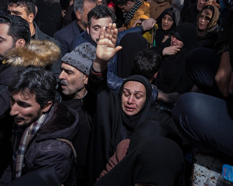 A woman raises her hand in a group of mourners. | Newsha Tavakolian—Magnum Photos for TIME