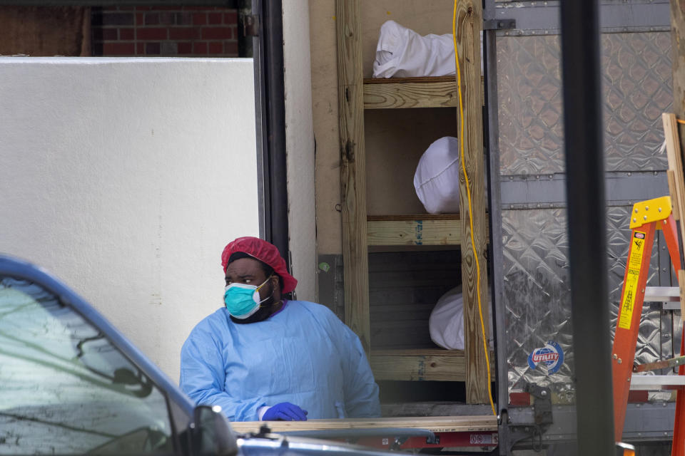 Medical personnel prepare to transport a body from a refrigerated container at Kingsbrook Jewish Medical Center, Wednesday, April 8, 2020, in the Brooklyn borough New York. From speculation that the coronavirus was created in a lab to a number of hoax cures, an overwhelming amount of false information about COVID-19 has followed the virus as it circled the globe over the past year. (AP Photo/Mary Altaffer)