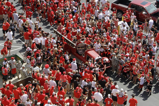 A vintage fire truck opens the walkway for the University of Louisville football team's march into the stadium before the season opening NCAA college football game against unranked Ohio University in Louisville, Ky., Sunday, Sept. 1, 2013. (AP Photo/Garry Jones)