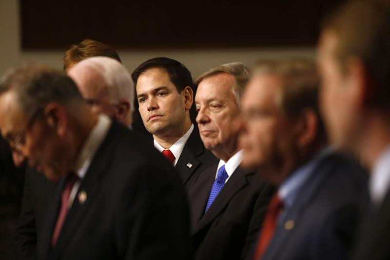 """FILE - In this April 18, 2013 file photo, Sen. Marco Rubio, R-Fla., center, and other members of immigration reform's bipartisan """"Gang of Heat,"""" appear at a Capitol Hill news conference in Washington. Passage of the landmark immigration bill won't be simple. Presidential ambitions alone will see to that, as Rubio, for one, attempts a political straddle while other potential GOP presidential candidates firmly oppose the measure. Rubio, who helped negotiate the bipartisan bill, has recently called for changes as he tries to keep faith with tea party supporters and other conservatives who will vote in the 2016 primaries and caucuses. Speaking at left is Sen. Charles Schumer, D-N.Y. (AP Photo/Charles Dharapak, File)"""