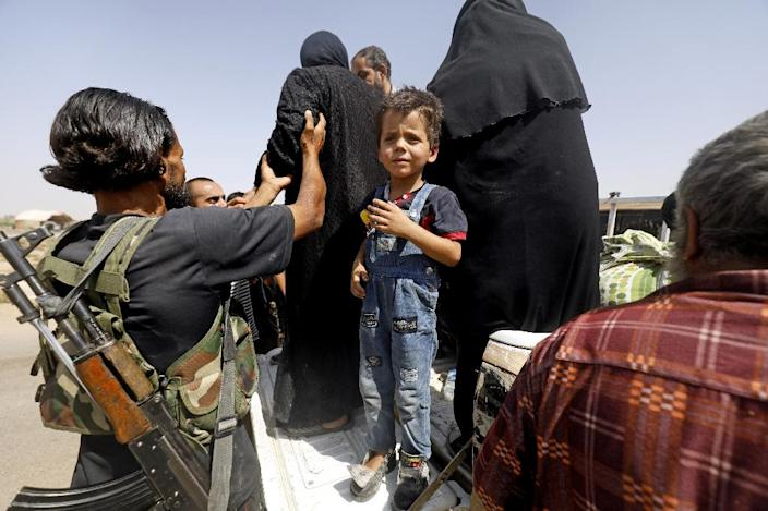Displaced Syrians who fled from the Islamic State (IS) group's stronghold of Raqa arrive in nearby village of Hawi al-Hawa on August 8, 2017 (AFP Photo/Delil souleiman)