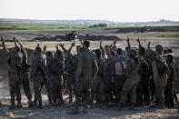 Israeli soldiers cheer as they take photos of themselves at an artillery position along the Israel Gaza border, Monday, May 17, 2021. (AP Photo/Heidi Levine)