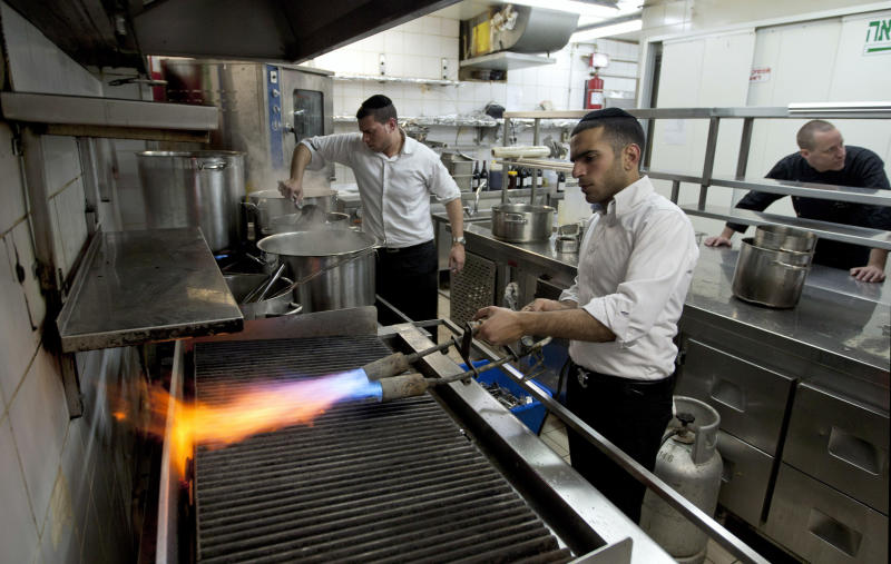 In this Thursday April 5, 2012 photo, chef Noam Dekkers , in the back, watches workers of the Tel Aviv-Jaffa rabbinate blow-torch the grill stove in one of the kitchens in Liliyot restaurant making it kosher for the Jewish holiday of Passover, in Tel Aviv, Israel. The Jewish springtime holiday Passover is known as a festival of freedom, but its hallmark is a litany of dietary restrictions centered on not eating leavened bread for a week. The rules are so elaborate that chefs who want to observe the ritual law must prepare weeks before, cleaning away every last crumb, buying up doubles of kitchen utensils, and planning menus without bread or regular flour. Standing back right is chef Noam Dekkers. (AP Photo/Ariel Schalit)
