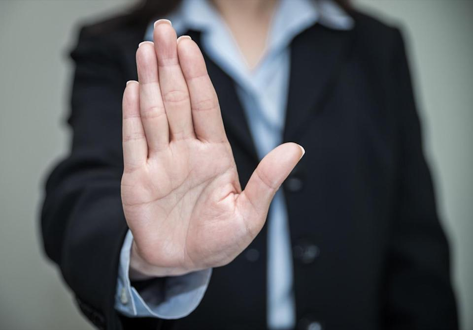 Woman in business suit showing her palm in grey background