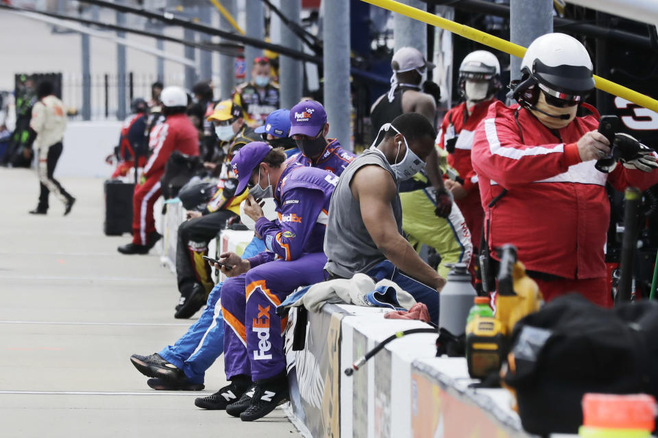 Crew members and officials wait in the pit area before the start of the NASCAR Cup Series auto race Sunday, May 17, 2020, in Darlington, S.C. (AP Photo/Brynn Anderson)
