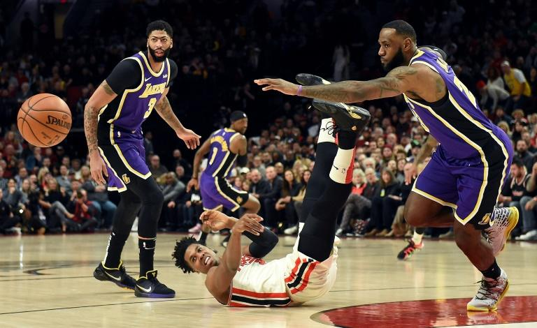 Portland's Hassan Whiteside is knocked to the floor as Anthony Davis and LeBron James of the Los Angeles Lakers go after the ball in the Lakers' NBA win over the Trail Blazers (AFP Photo/Steve DYKES)